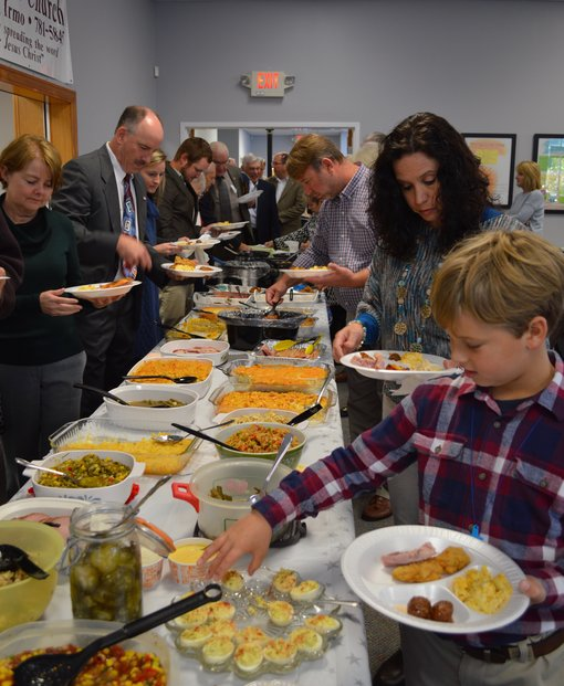 Families filling plates from a table of potluck dishes