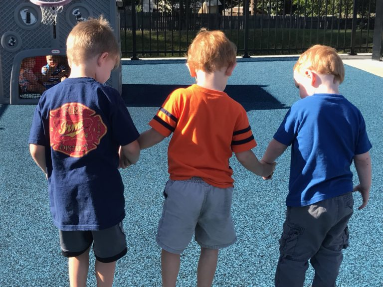 3 kids holding hands while walking