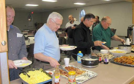 Men filling their plates at a prayer breakfast