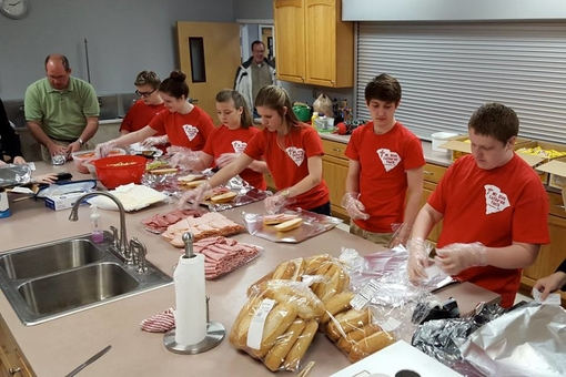 Teens preparing meals for others